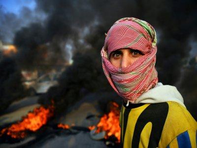 Un manifestant irakien bloque une route dans la ville irakienne de Najaf (sud), le 27 novembre 2019 - Haidar HAMDANI [AFP]