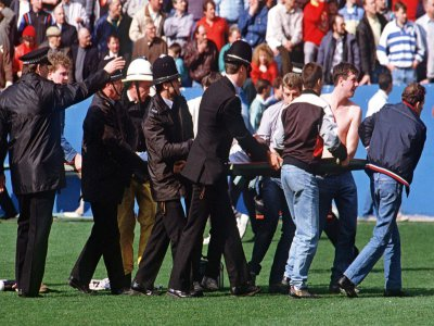 Des policiers et des supporters aident à évacuer des blessés du stade d'Hillsborough (Royaume-Uni) le 15 avril 1989, où une bousculade a coûté la vie à 96 personnes    STRINGER [AFP/Archives]