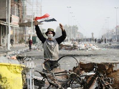 Un manifestant irakien brandit le drapeau national, dans la ville sainte de Najaf, le 1er décembre 2019    Haidar HAMDANI [AFP]