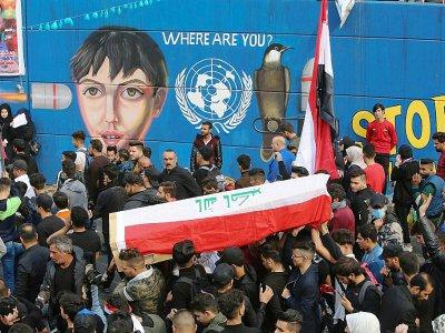 Des Irakiens portent le cercueil d'un jeune manifestant tué la veille, le 1er décembre 2019 sur la place Tahrir, dans le centre de Bagdad    SABAH ARAR [AFP]