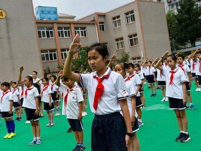Des élèves à Shangaï chantent l'hymne chinois lors d'une cérémonie dans leur école, en septembre 2017 - Chandan KHANNA [AFP/Archives]