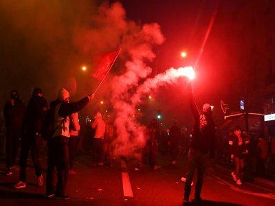 Un manifestant brandit une fusée rouge pendant la manifestation jeudi à Paris contre la réforme des retraites qui a vu des centaines de milliers de personnes descendre dans les rues - Alain JOCARD [AFP]