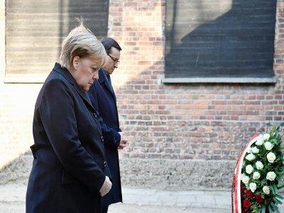 La chancelière allemande Angela Merkel et le Premier ministre polonais   Mateusz Morawiecki se recueillent après avoir déposé une gerbe au camp nazi d'Auschwitz-Birkenau, en Pologne, le 6 décembre 2019    John MACDOUGALL [AFP]