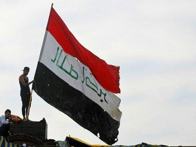 Un manifestant brandit le drapeau irakien dans la capitale Bagdad le 6 novembre 2019 - AHMAD AL-RUBAYE [AFP]