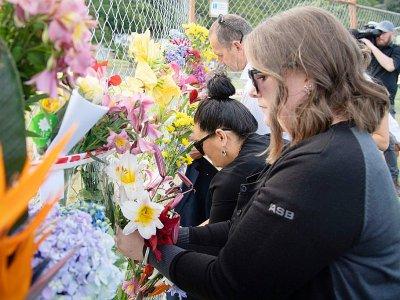 Des fleurs sont déposées sur le rivage près de l'endroit d'où partent les touristes pour White Island, à la mémoire des victimes de l'éruption du volcan en Nouvelle-Zélande, le 10 décembre 2019    Marty MELVILLE [AFP]