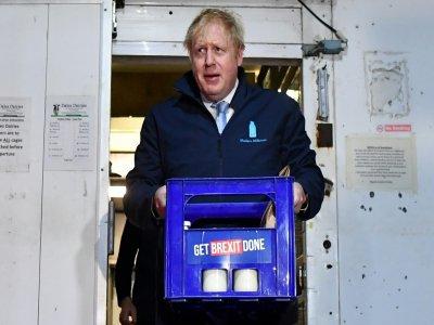 Le Premier ministre Boris Johnson porte un pack de bouteilles de lait  à Guiseley, dans le cadre de sa campagne électorale le 11 décembre 2019    Ben STANSALL [POOL/AFP]