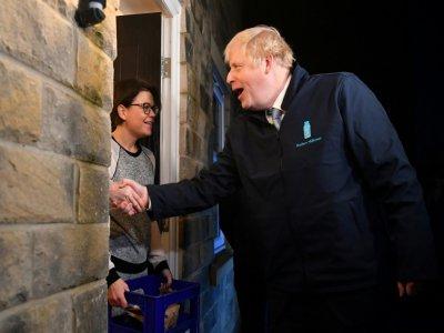 Boris Johnson apporte une bouteille de lait à Debbie Monaghan à Guiseley, le 11 décembre 2019 dans le cadre de sa campagne électorale    Ben STANSALL [POOL/AFP]