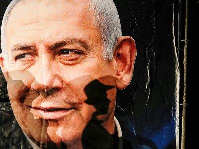 L'ombre d'un passant se projette sur un portrait du Premier ministre israélien Benjamin Netanyahu, à Jérusalem, le 11 décembre 2019    AHMAD GHARABLI [AFP]