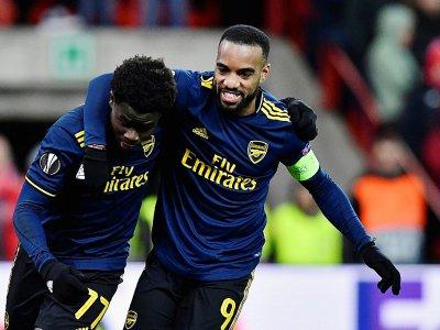 Les attaquants d'Arsenal Bukayo Saka (g) et Alexandre Lacazette heureux après un but du premier sur le terrain du Standard de Liège en Ligue Europa, le 12 décembre 2019 - JOHN THYS [AFP]