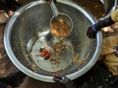 Des mains posées sur une assiette presque vide, servie à des familles dans le village de Merine Dakhar (Sénégal), le 29 mai 2008    GEORGES GOBET [AFP/Archives]