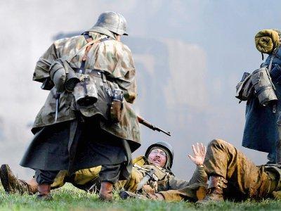 Un acteur en uniforme allemand de la Seconde Guerre mondiale lors d'une scène de capture de soldats américains durant une reconstitution de la bataille des Ardennes, à Hardigny (Belgique) le 15 décembre 2019    JOHN THYS [AFP]
