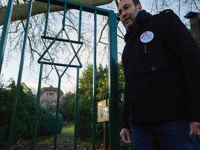 """Un volontaire des """"veilleurs de mémoire"""", Lionel Godmet, devant la porte du cimetière juif de Jungholtz, dans l'est de la France, le 10 décembre 2019    SEBASTIEN BOZON [AFP]"""