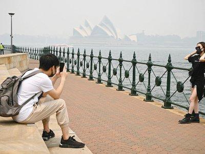 Des touristes portent des masques en raison des fumées toxiques liées aux incendies de forêts, le 10 décembre 2019 à Sydney, en Australie    PETER PARKS [AFP/Archives]