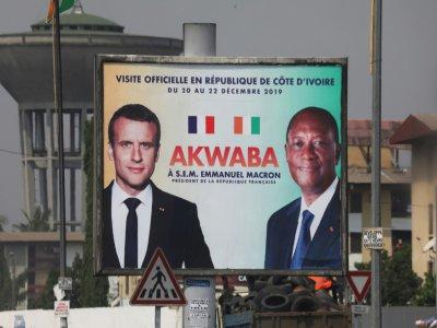 Une affiche montrant Emmanuel Macron (g) et son homologue ivoirien Alassane Ouattara à Abidjan le 19 décembre 2019    Ludovic MARIN [AFP]
