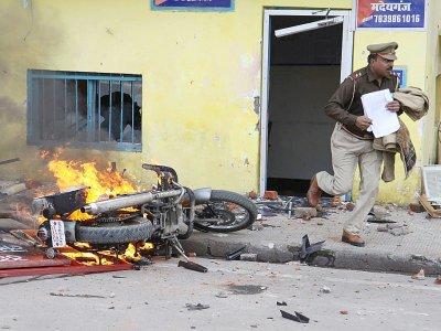 Un policier indien s'enfuit, tenant des documents, hors d'un commissariat attaqué par des manifestants contre la nouvelle loi sur la citoyenneté, à Lucknow le 19 décembre 2019    STR [AFP]