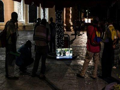 Des passants regardent la télévision dans la rue, place Bolivar, le 13 décembre 2019 à Caracas, au Venezuela    Yuri Cortez [AFP]