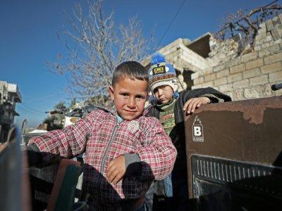 Les enfants d'Abou Ismail  montent à l'arrière d'un véhicule pour fuir la ville de Maaret al-Noomane, dans la province syrienne d'Idleb (nord-ouest), le 20 décembre 2019.    Omar HAJ KADOUR [AFP]