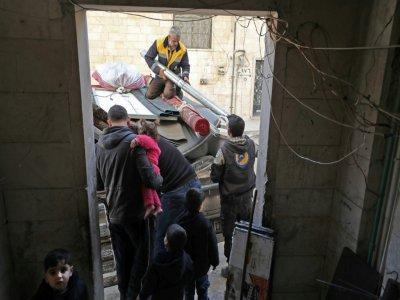 Des secouristes des Casques blancs aident Abou Oussama avant son départ de Maaret al-Noomane, dans la province syrienne d'Idleb (nord-ouest), le 20 décembre 2019.    Omar HAJ KADOUR [AFP]