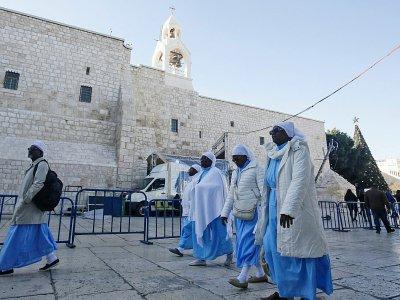 Des pélerins chrétiens visitent la Basilique de la Nativité le 24 décembre 2019 à Bethléem, en Cisjordanie occupée - HAZEM BADER [AFP]