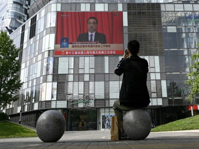 Un homme regarde la transmission en direct de la session inaugurale du parlement chinois à Pékin, le 22 mai 2020