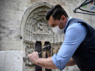 Un tailleur de pierre  montre les gestes médievaux devant des visiteurs dans le cadre d'un atelier et du projet de reconstruction de la flèche de la basilique Saint-Denis, devant l'édifice à Saint-Denis, le 5 juin 2020    Anne-Christine POUJOULAT [AFP]