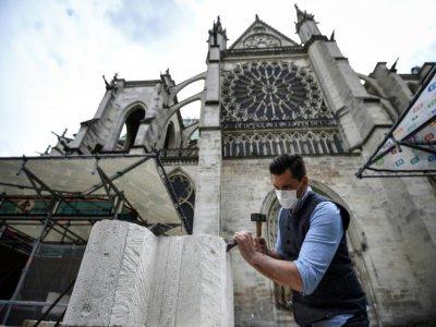 Un tailleur de pierre explique ses gestes à des visiteurs devant la basilique Saint-Denis, le 5 juin 2020    Anne-Christine POUJOULAT [AFP]