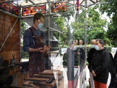 Un forgeron explique son travail et montre les gestes médiévaux à des visiteurs, le 5 juin 2020 devant la basilique de Saint-Denis    Anne-Christine POUJOULAT [AFP]