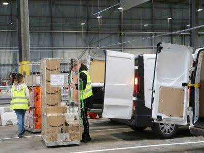 Placés dans des chariots selon les lieux de destination, les prestataires de livraison embarquent les colis dans leur véhicule pour les distribuer selon la tournée établie par Amazon.