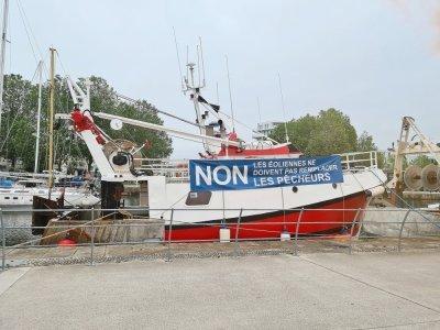 Des banderoles sont accrochées dans le port de Caen et des fumigènes bleus sont lancés en signe de revendication.