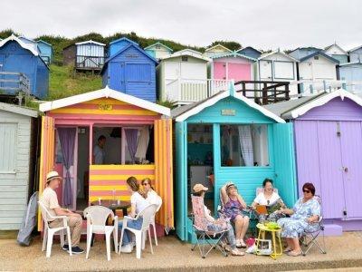 Des personnes assises devant des cabines de plage, le 15 juillet 2021à  Walton-on-the-Naze    Justin TALLIS [AFP]