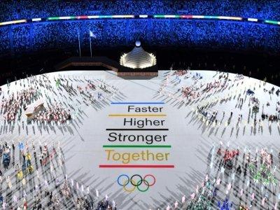 """La devise des Jeux Olympiques """"Plus vite, plus haut, plus fort"""" est projetée au milieu des délégations de sportifs du monde entier, lors de la cérémonie d'ouverture des Jeux Olympiques, le 23 juillet 2021 à Tokyo    François-Xavier MARIT [AFP]"""