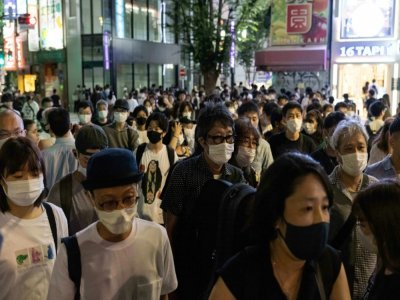 Une foule masquée marche dans le districk de Shinjuku, le 17 juillet 2021 à Tokyo    Yuki IWAMURA [AFP/Archives]
