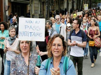 """Une femme défile le 17 juillet 2021 à Paris avec une pancarte  """"Non au pass nazitaire"""", pour dénoncer l'instauration d'un pass sanitaire annoncée par l'exécutif entre autres mesures visant à lutter contre l'épidémie de Covid-19    GEOFFROY VAN DER HASSELT [AFP]"""