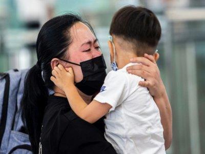 Une femme dit adieu à un jeune enfant à l'aéroport de Hong Kong le 19 juillet 2021    ISAAC LAWRENCE [AFP]