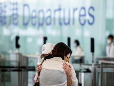 Des habitants disent adieu à leurs proches avant de prendre un vol pour Londres à l'aéroport de Hong Kong le 17 juillet 2021    ISAAC LAWRENCE [AFP]