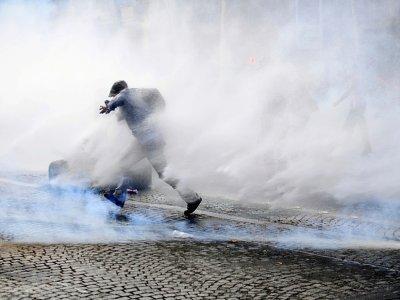 Un manifestant entouré de gaz lacrymogène court lors de heurts au cours d'une manifestation anti-pass sanitaire le 24 juillet 2021 à Paris    Alain JOCARD [AFP]