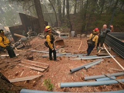Jon Cappleman en pleine conversation avec des pompiers venus inspecter les environs de sa propriété, à Twain, en Californie, le 26 juillet 2021    Robyn Beck [AFP]