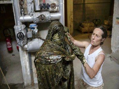 La sculptrice Frédérique Nalbandian réalise  une oeuvre faite de tissus et de savon de Marseille dans la plus ancienne savonnerie de Marseille, le 22 juillet 2021    Christophe SIMON [AFP]