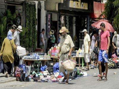 Des personnes font des achats auprès de marchands le long d'une route au marché populaire de Bab el-Fellah, à Tunis, le 28 juillet 2021 - FETHI BELAID [AFP]