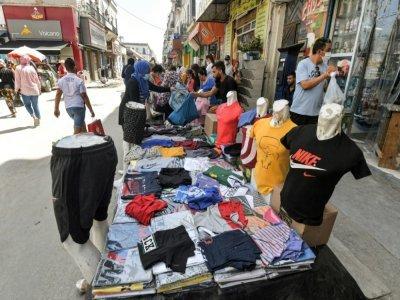 Une femme achète des vêtements à un marchand au souk de Bab el-Fellah, à Tunis, le 28 juillet 2021 - FETHI BELAID [AFP]