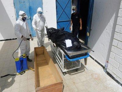 Sur cette photo d'archive prise le 04 juillet 2021, des employés de la municipalité tunisienne désinfectent le corps d'une victime du Covid-19 à l'hôpital Ibn al-Jazzar dans la ville de Kairouan, dans le centre-est de la Tunisie    FETHI BELAID [AFP/Archives]