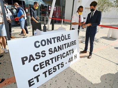 Le porte-parole du gouvernement Gabriel Attal (D) présente son pass sanitaire lors d'une visite dans un cinéma de Montpellier le 29 juillet 2021    Pascal GUYOT [AFP]