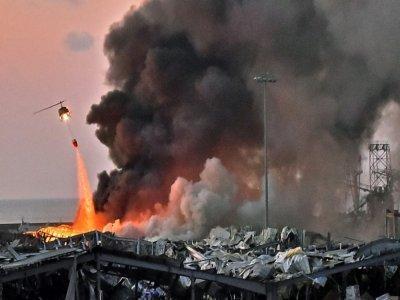 Un hélicoptère aide à éteindre le feu après l'explosion au port de Beyrouth, le 4 août 2020    STR [AFP/Archives]