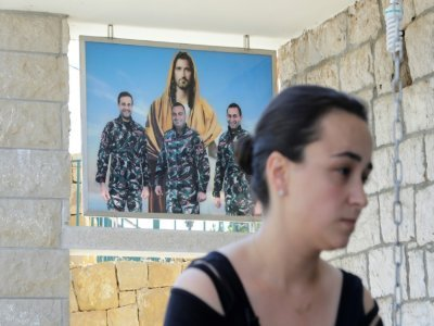 L'époux, le frère et le cousin de Karlen Hitti Karam, montrés dans une photo derrière la jeune femme qui les a perdus tous trois -des pompiers- dans l'explosion du 4 août 2020 au port de Beyrouth    JOSEPH EID [AFP/Archives]