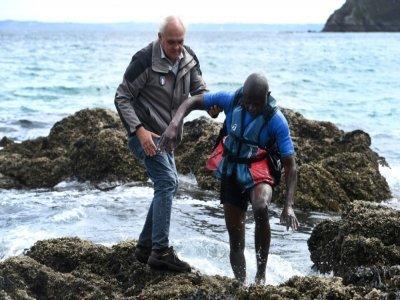 Didier Cadiou aide un kayakiste qui a chaviré à proximité de la plage de l'Île Vierge sur la presqu'île de Crozon dans le Finistère, le 29 juillet 2021    Fred TANNEAU [AFP]