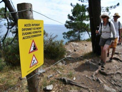 Des randonneurs à proximité d'une une pancarte indiquant l'interdiction d'accès à la plage de l'Ile Vierge à Crozon dans le Finistère, le 29 juillet 2021    Fred TANNEAU [AFP]