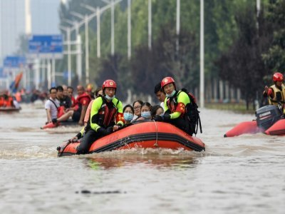 Des secouristes évacuant des habitants de la ville inondée de Zhenzhou en Chine, le 22 juillet 2021    STR [AFP/Archives]