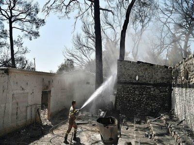 Un pompier grec lutte contre le feu sur un site abandonné du Club Méditerranée à Lambiri, près de Patras, le 1er août 2021    LOUISA GOULIAMAKI [AFP]