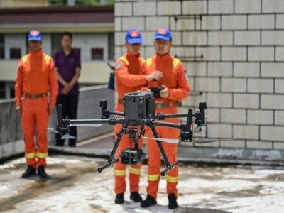 Des gardes forestiers du Yunnan manipulent un drone chargé de surveiller la migation des éléphants, le 23 juillet 2021 - Hector RETAMAL [AFP]