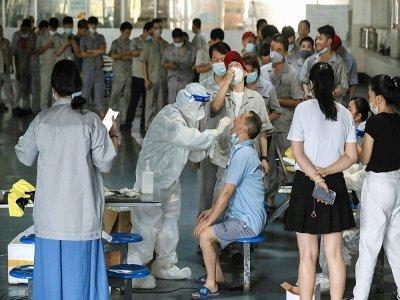 Centre de test Covid-19 dans le réfectoire d'une usine automobile le 4 août 2021 à Wuhan, en Chine, épicentre de l'épidémie en 2019    STR [AFP]